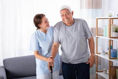 caregiver assisting senior man using walking frame