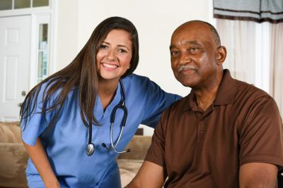 senior man and a caregiver smiling