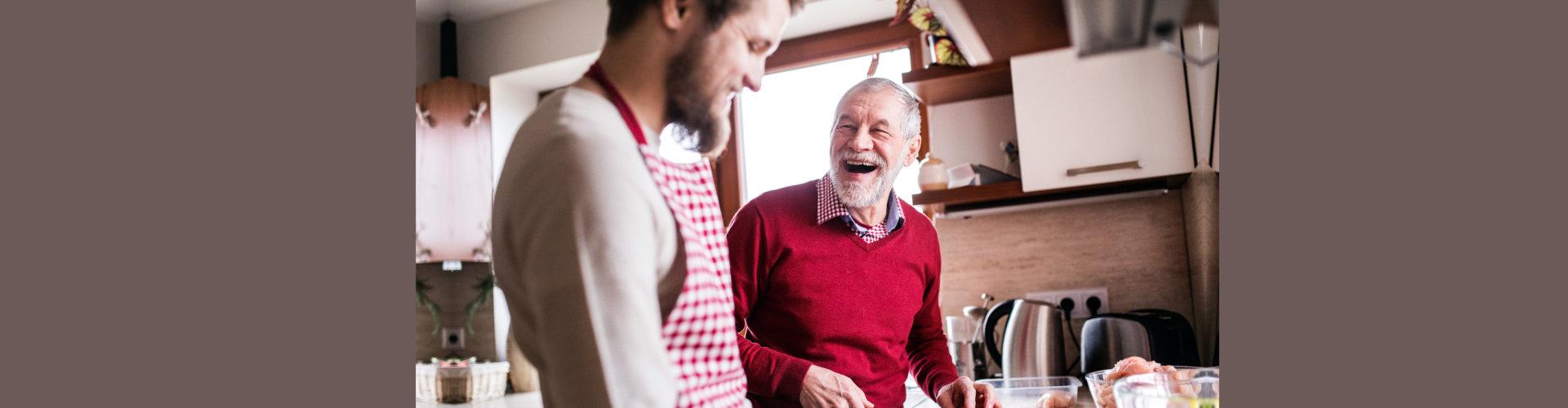 senior man and a caregiver cooking