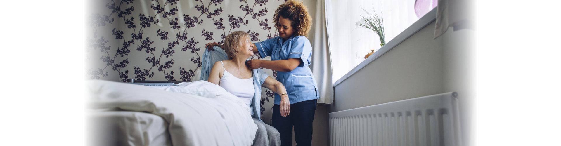 caregiver making senior woman's clothes