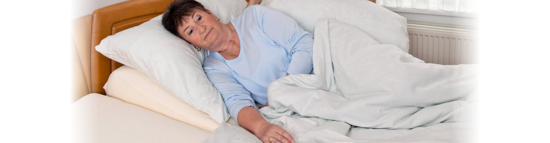 senior woman laying in bed
